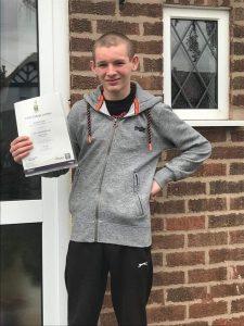 Daniel holding his Bronze Arts Award certificate