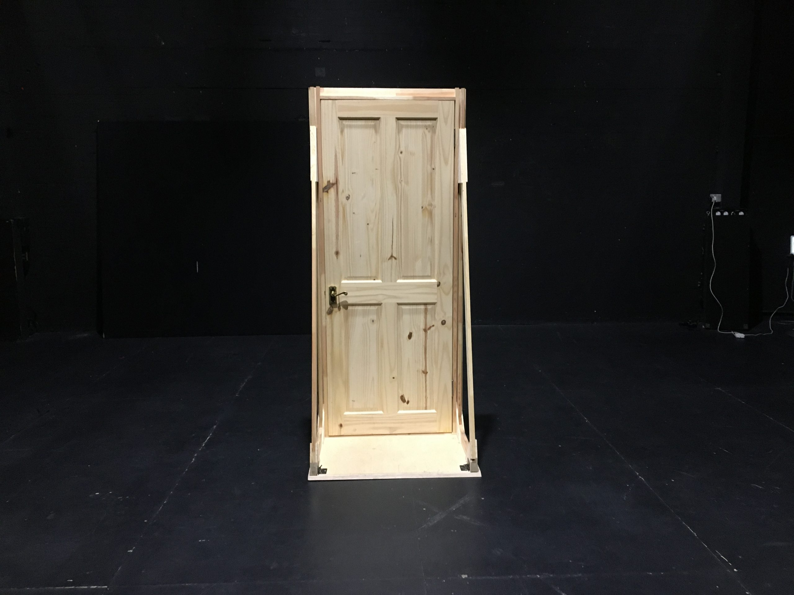 A wooden door in a black room.