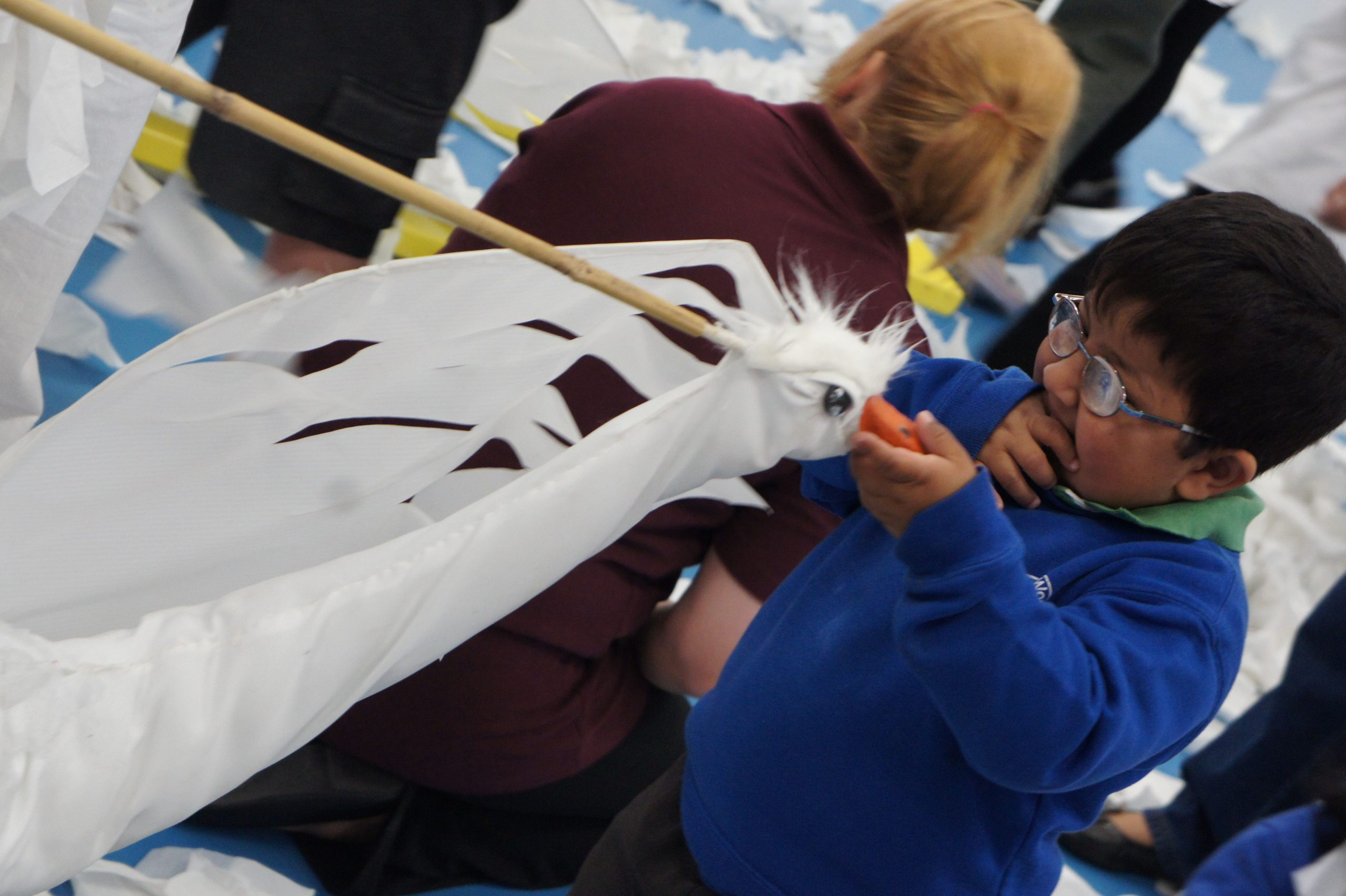 A little boy, asian, wearing glasses and wearing a blue school jumper holds out his hand to touch a swan puppet. In the background a white female with red hair and a red cardigan is kneeling down. The floor is covered in white tissue paper.