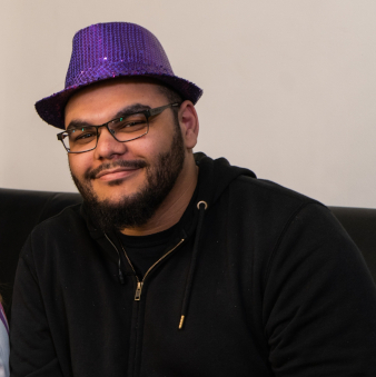 Ashley wears a sparkling purple hat and smiles to camera