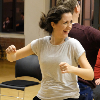 Bethan smiles while standing back to back with a workshop participant