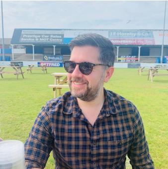 Daniel smiles while wearing sunglasses in an open sports field