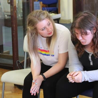 Grace plays the role of supportive friend in rehearsal, leaning attentively towards another actor, who looks troubled.