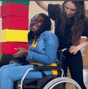 Hannah adds another soft block to an impossibly large tower which is being balanced by a workshop participant in a wheelchair