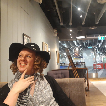 Hazel wears a big floppy hat and smiles