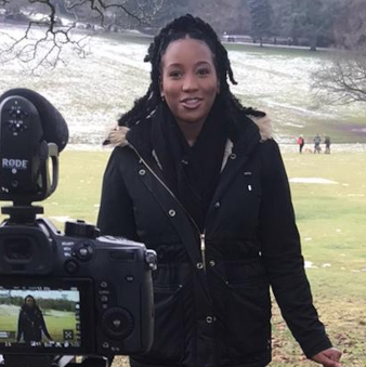 Jenara stands in a park, facing a camera, about to start filming