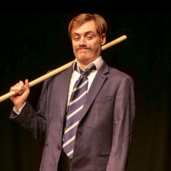 Luke, wearing a suit and tie, holds a long stick and looks unimpressed
