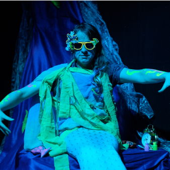 Matthew wears a mermaid outfit with bright yellow sunglasses, staring ominously