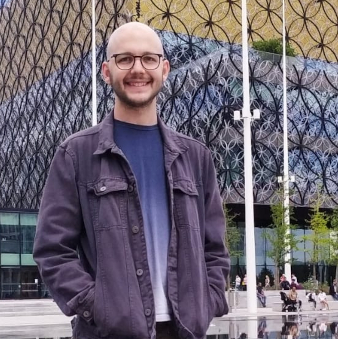 Ryan, smiling with hands in their pockets, stands in front of the Library of Birmingham