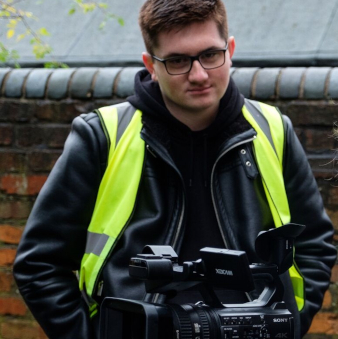 Sean, wearing a high-vis jacket, leans towards a film camera